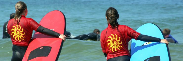 Two novice surfers wading towards the waves with their surfboards